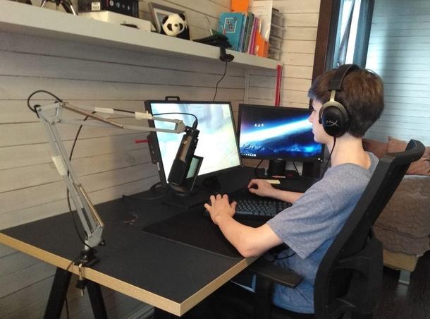 «Пострадавший» стол пришлось перевернуть, чтобы не мешал играть — теперь дырка находится рядом с монитором. На фото также видна самодельная микрофонная стойка из старой лампы — ее сделал для брата Жора